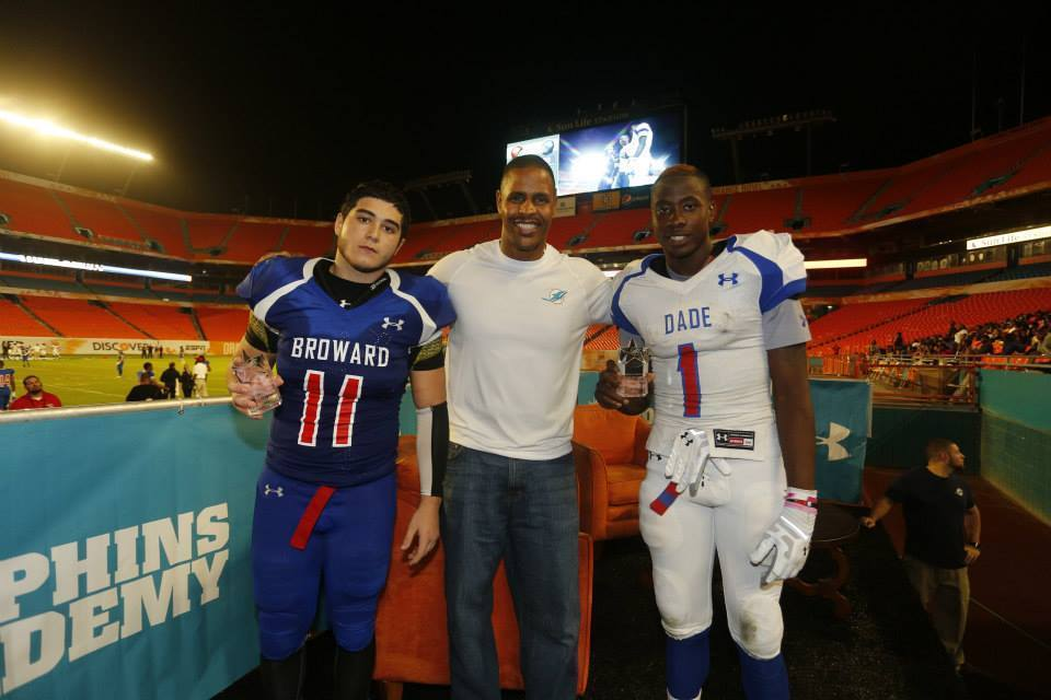 Game MVPs take a bow with Twan Russell, Miami Dolphins Senior Director of Community Affairs. South Dade quarterback Kahlil Render, right, receives Offensive MVP award while University School linebacker Andrew Korakakos receives the Defensive MVP Award.