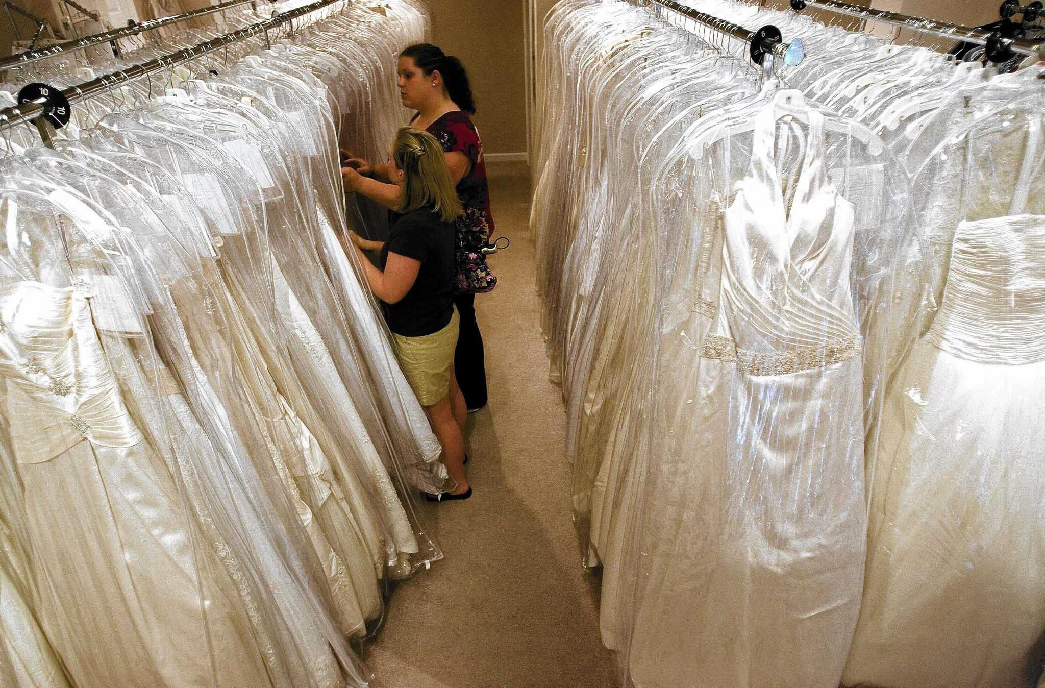 Customers to Blush Bridal Consignment Boutique in Port Warwick search through the racks of used bridal gowns Thursday. A used dress is one of the ways many brides are saving money. No Mags, No Sales, No Internet, No TV
