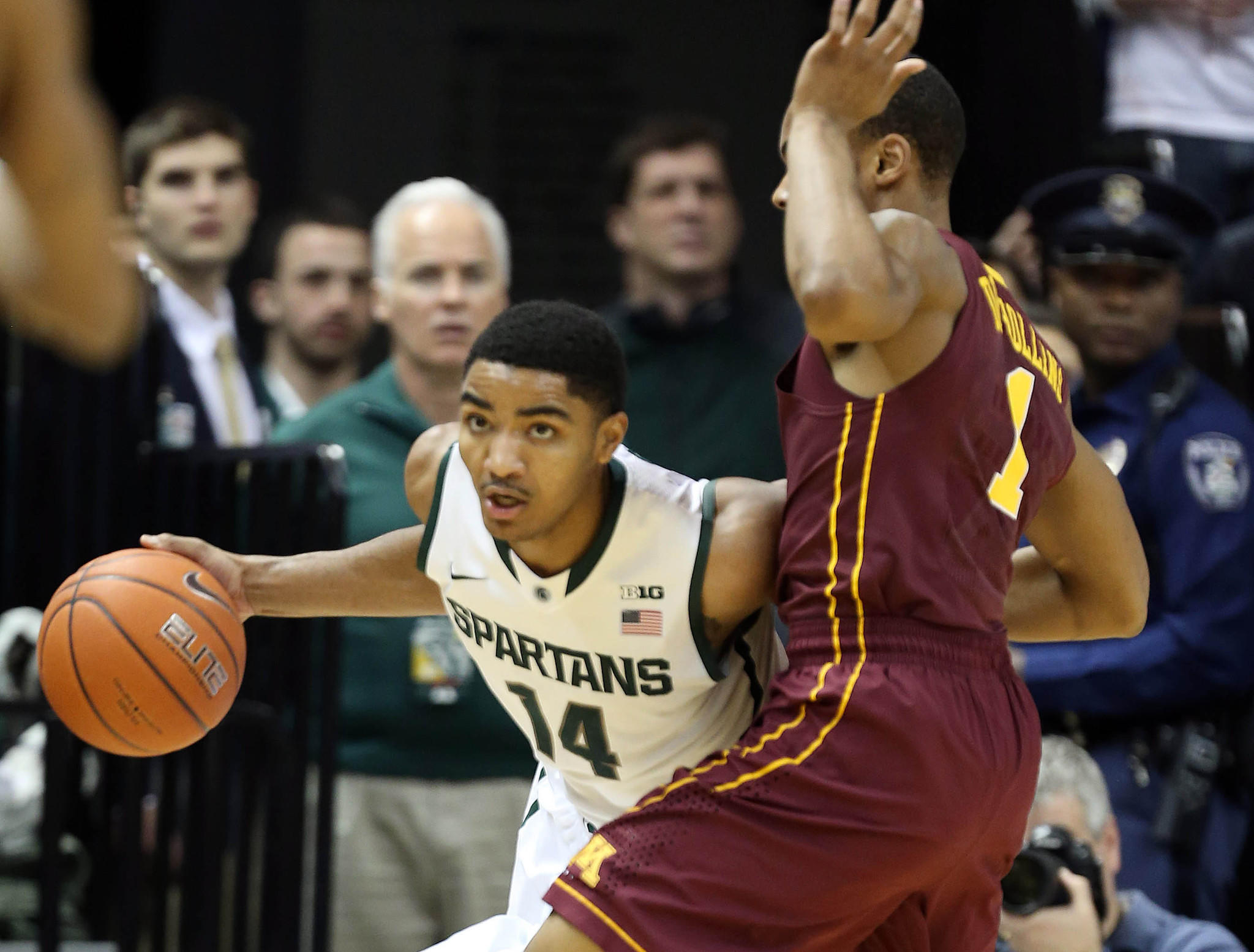 Michigan State Spartans guard Gary Harris (14) brings the ball up court against Minnesota Golden Gophers guard Andre Hollins (1).