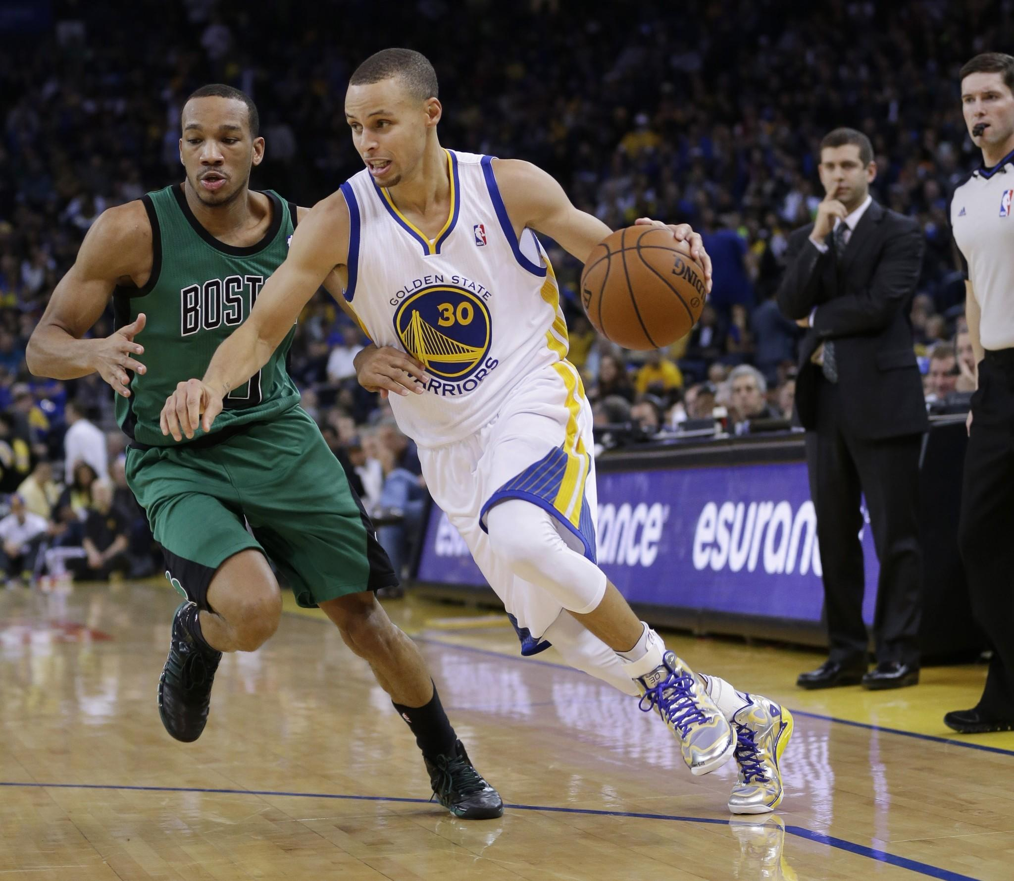 Stephen Curry dribbles past Avery Bradley during the second half of Golden State's 99-97 win Friday over the Boston Celtics.