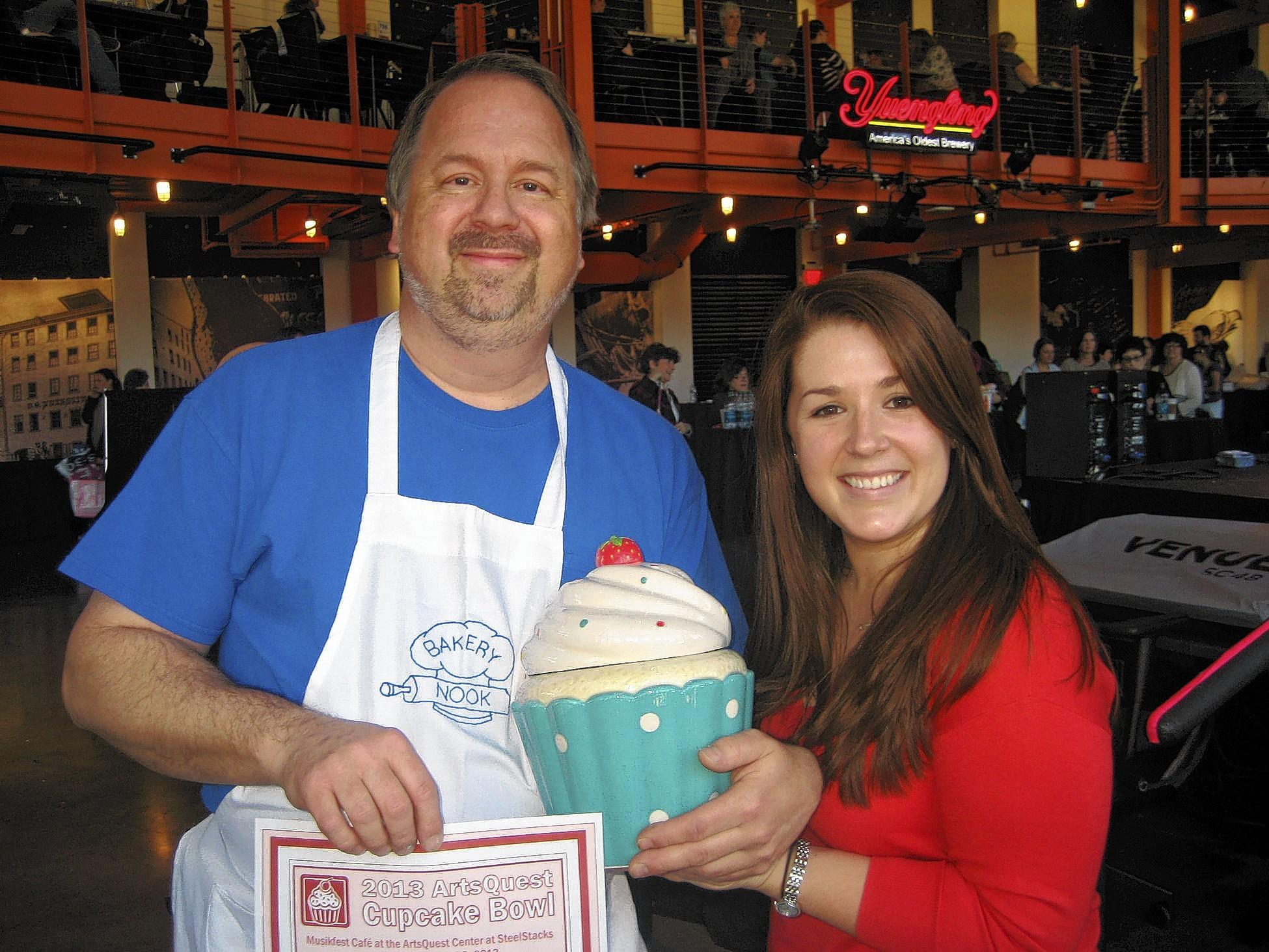 Barry Kuntz from the Bakery Nook is congratulated by Samantha Kulp, ArtsQuest membership manager, for taking the People's Choice Award at ArtsQuest's sold-out Cupcake Bowl II on Dec. 28 in the Musikfest Cafe at the ArtsQuest Center at SteelStacks. The Nook offered up a Sweet Strawberry Crème Cupcake.
