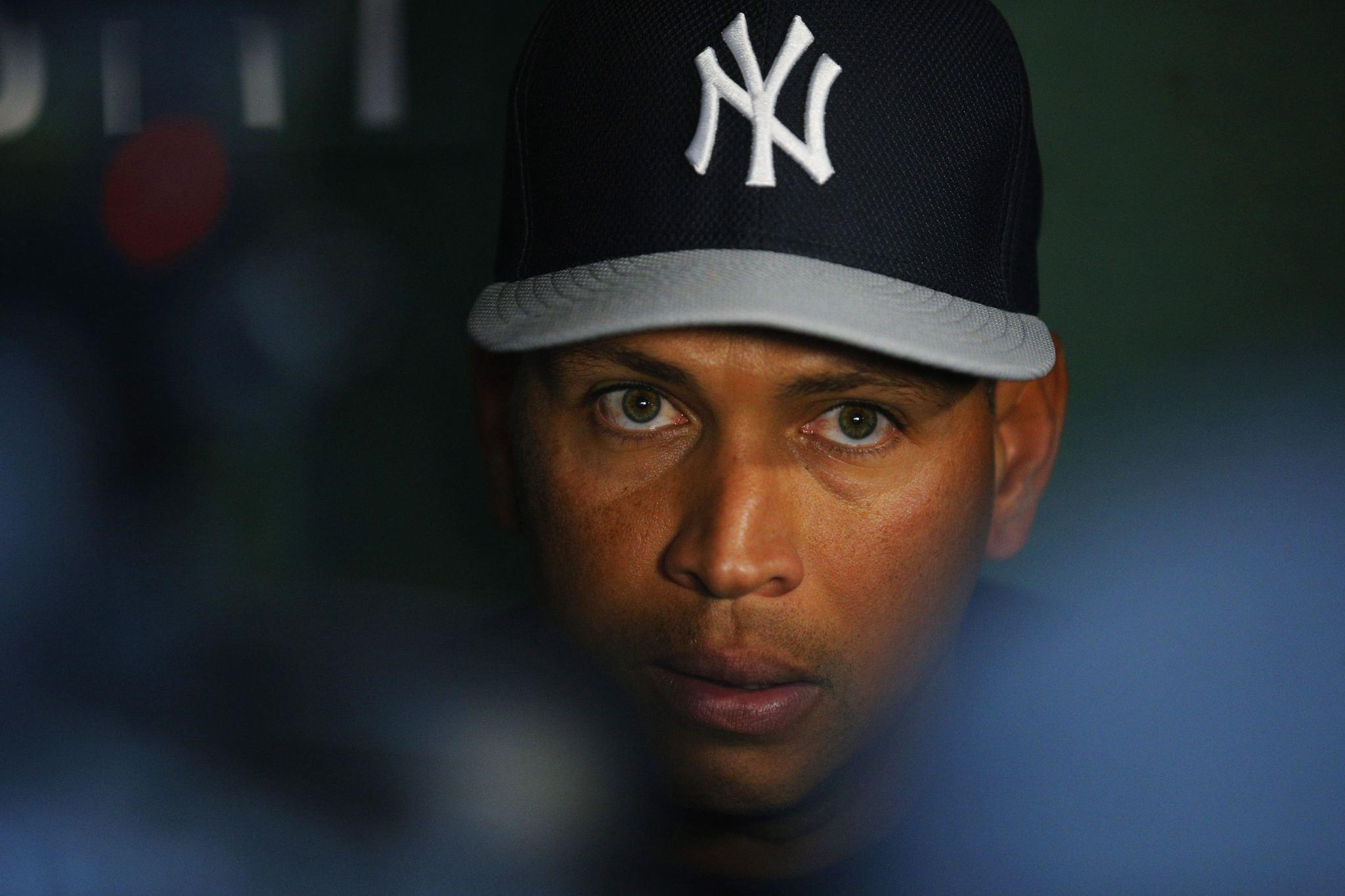 New York Yankees third baseman Alex Rodriguez, shown talking to reporters before a game against the Boston Red Sox last August, was suspended for all of the 2014 season Saturday.