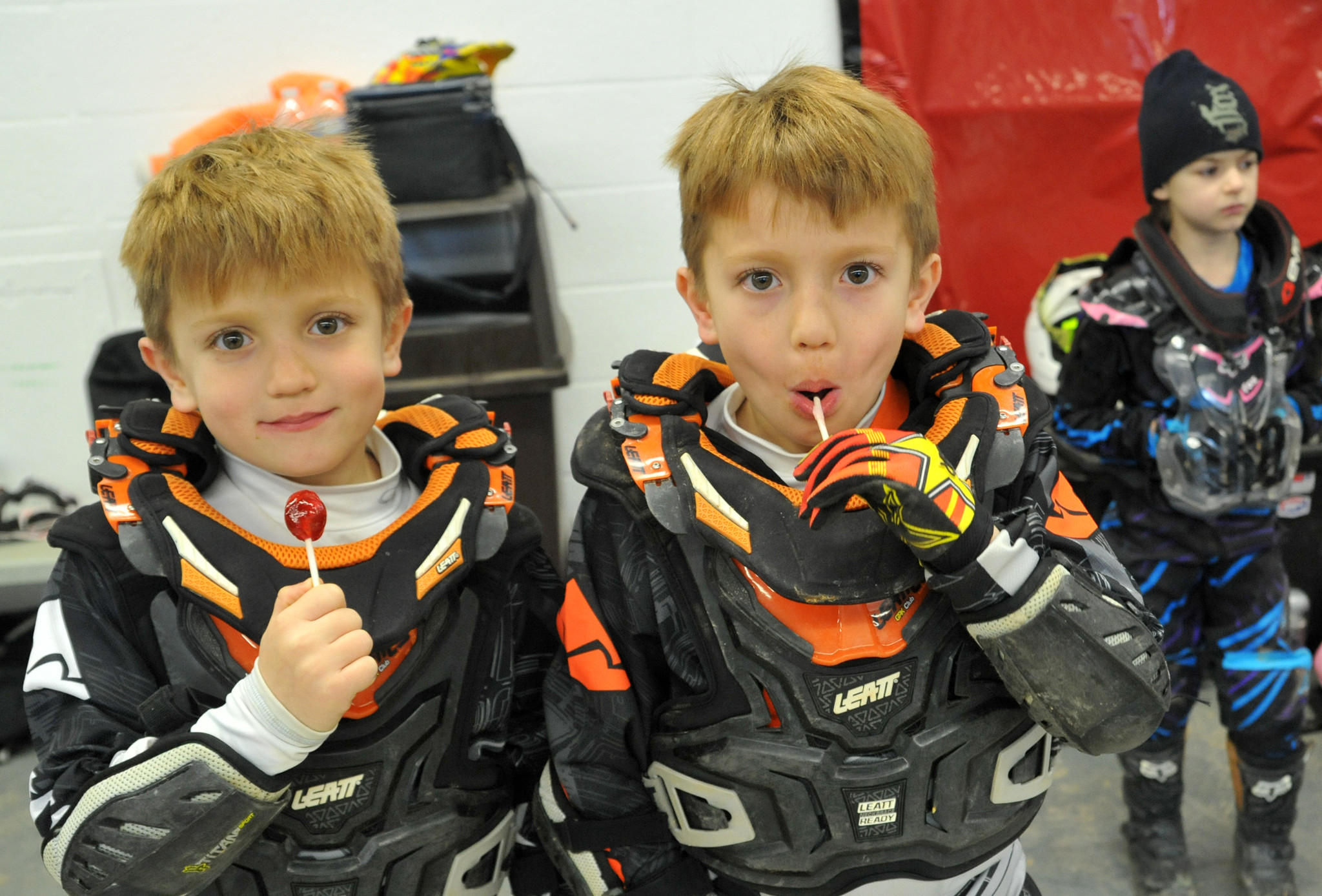 Twins Dominic, left, and Colton Stallings, 6, of Huntingtown, MD, take a lollipop break between races in the Baltimore AMSOIL Arenacross event at the Baltimore Arena.