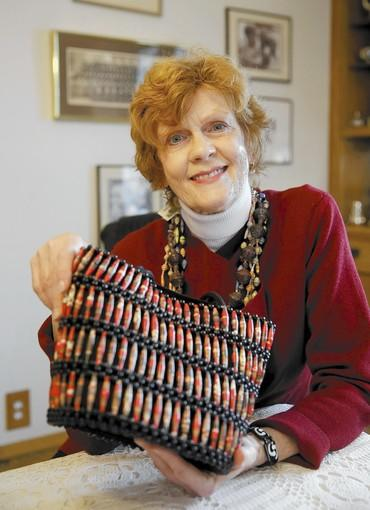 Keen Harrison, the founder of Project Harambee, holds a beaded purse and wears necklaces made by women in Kenya to help fund care for the women.