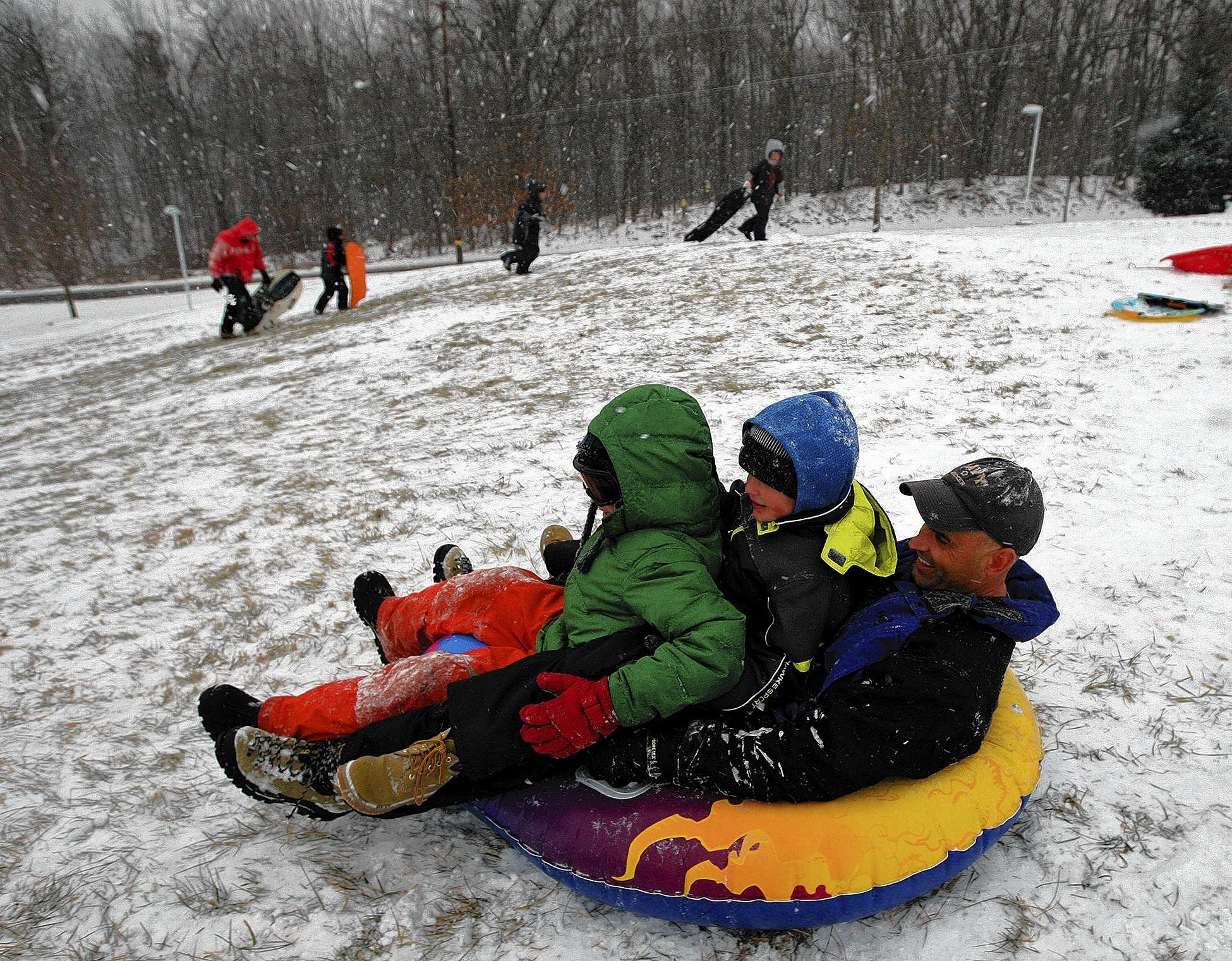 Brad Dunham (right), Dan Reagan (center), 7, and Eli Dunham, 9, all of Center Valley, get ready to take off while sledding at DeSales University.