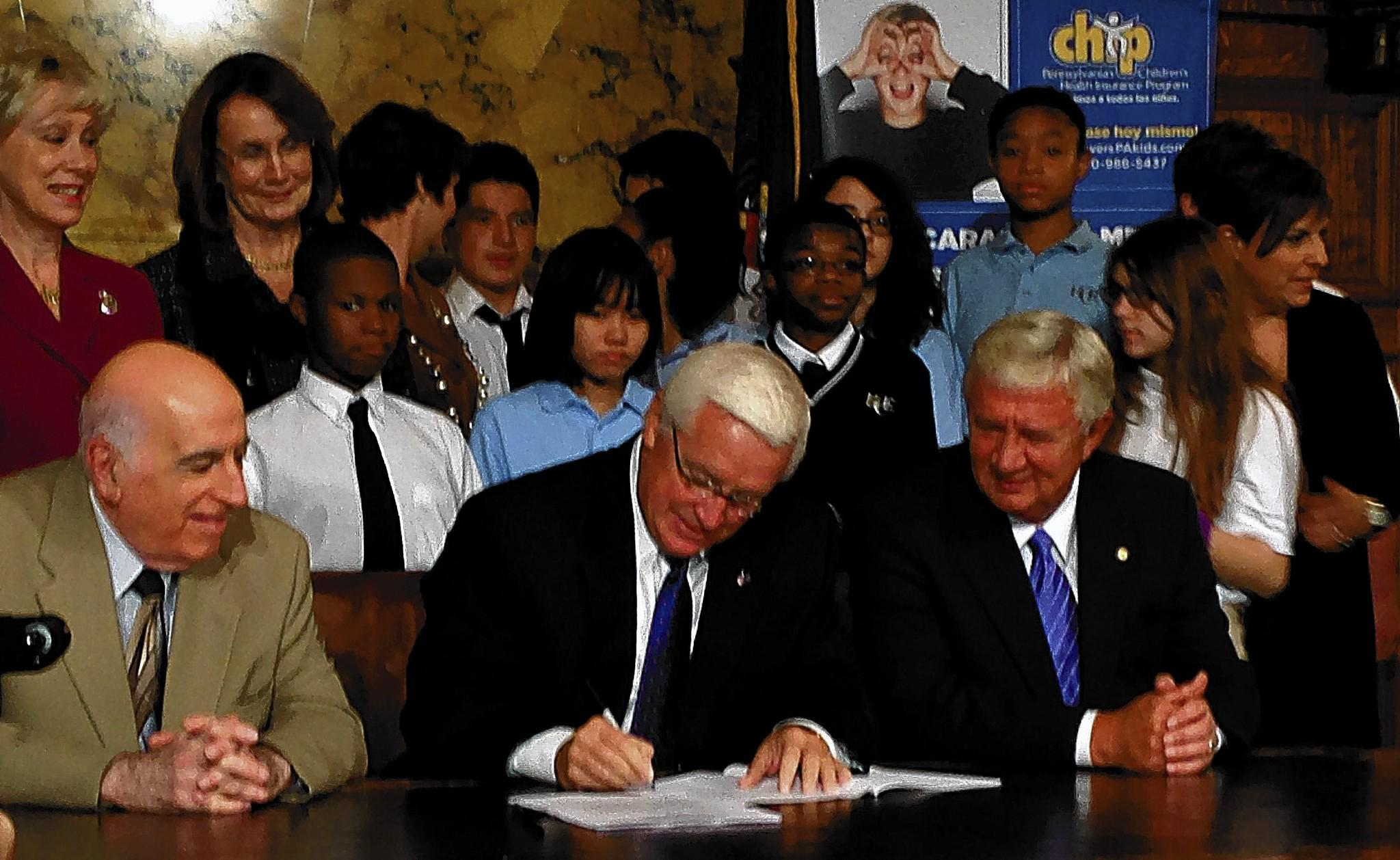Gov. Corbett, flanked by Rep. Nick Micozzie, R-Delaware, and Sen. Don White, R-Indiana, signs a law that ends a six-month wait for the Children's Health Insurance Program.