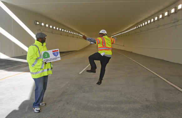 Caltrans officials Peter Jones, left, and Patrick Chandler celebrate the reopening of the underpass connecting the Glendale Freeway with the northbound 5 freeway in Los Angeles,