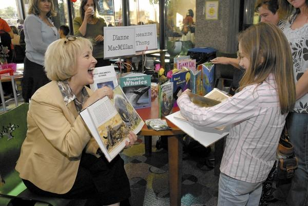 Author Dianne MacMillan shows off one of her books to Brooke Aguilar at a past Author's Festival at the Huntington Beach Central Library.