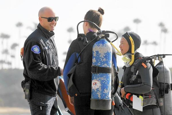 Marine Safety Lt. Kai Bond talks to scuba divers Victoria Eisenhart, 17, and Celeste Lau, 44, from left to right, before they head into the water at Crescent Bay Beach in Laguna Beach on Friday.