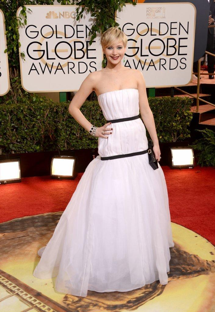 Actress Jennifer Lawrence poses in a Dior Haute Couture off-white silk evening gown at the 71st annual Golden Globe Awards.