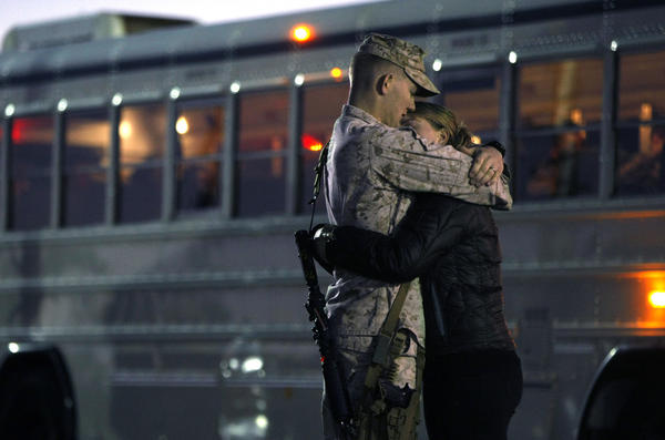 A young Marine and his wife embrace before he heads out to Afghanistan