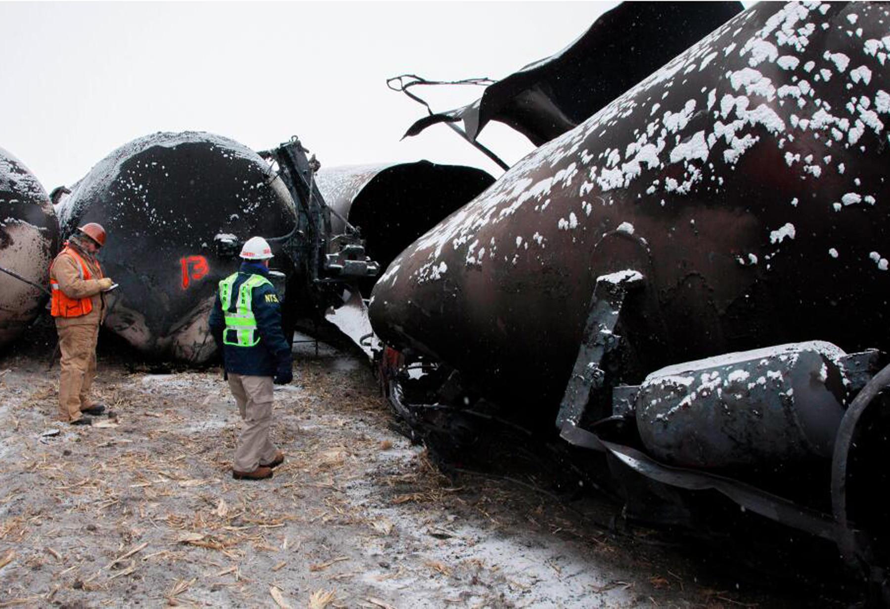 National Transportation Safety Board board member Robert Sumwalt, right, views damaged rail cars in Casselton, N.D., recently.