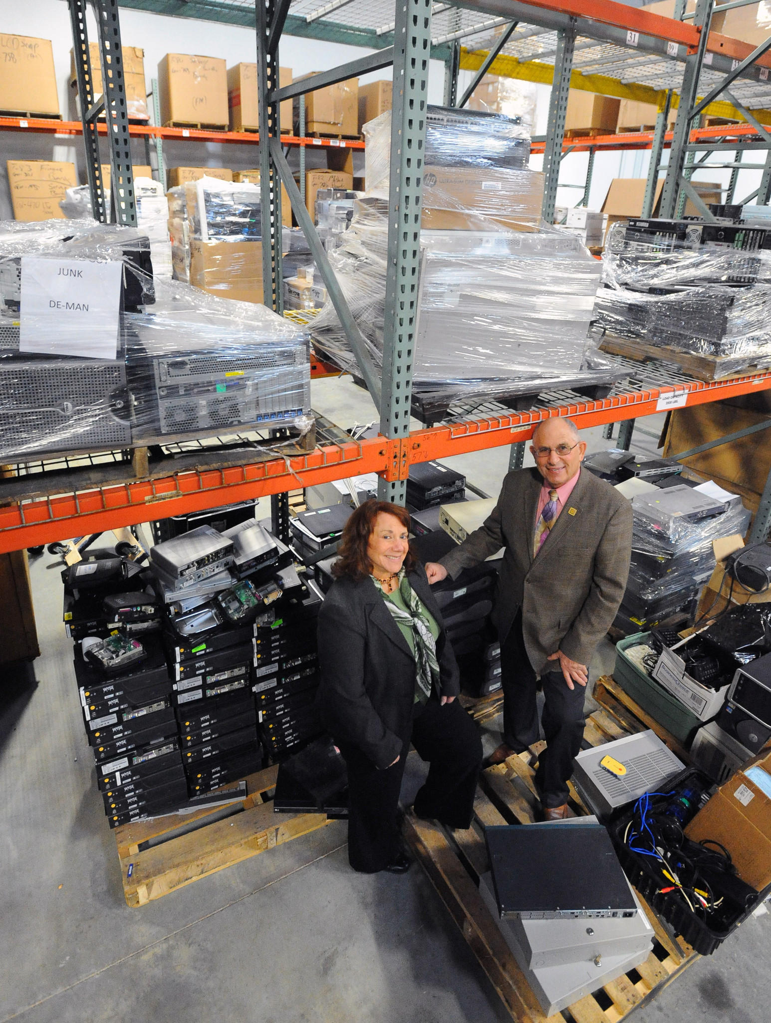 CEO Arleen Chafitz, left, and husband Steve Chafitz, president, run e-End, which specializes in the secure sanitization of electronic media and data residing on end of life equipment no longer used by government agencies, contractors services or businesses. The couple is pictured in the company's warehouse filled with degaussed computer electronics that could be recycled.