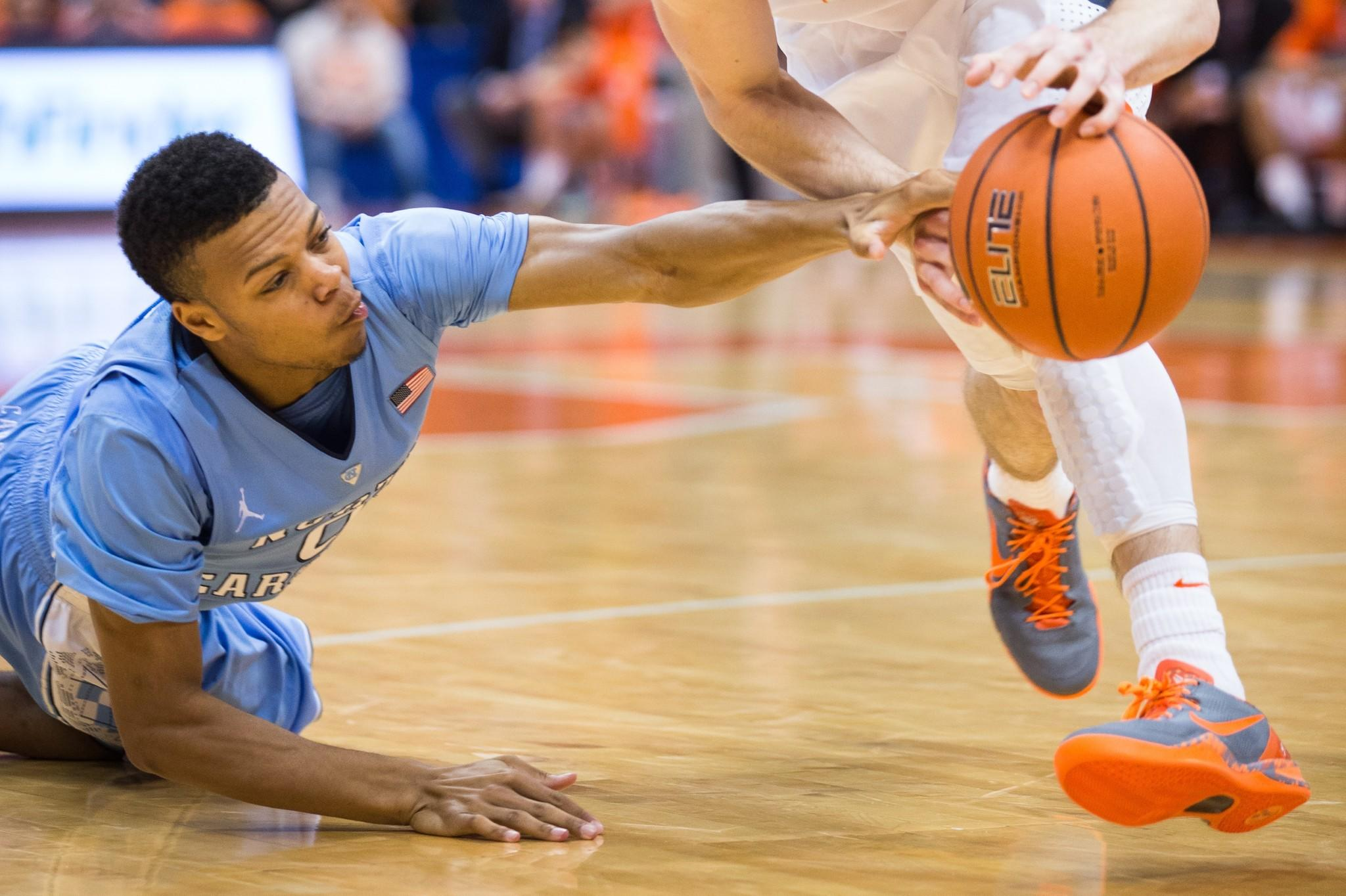 Nate Britt of the North Carolina Tar Heels reaches in unsuccessfully as Trevor Cooney of the Syracuse Orange dribbles past in the second half on January 11, 2014 at The Carrier Dome in Syracuse, New York. Syracuse defeats North Carolina 57-45.