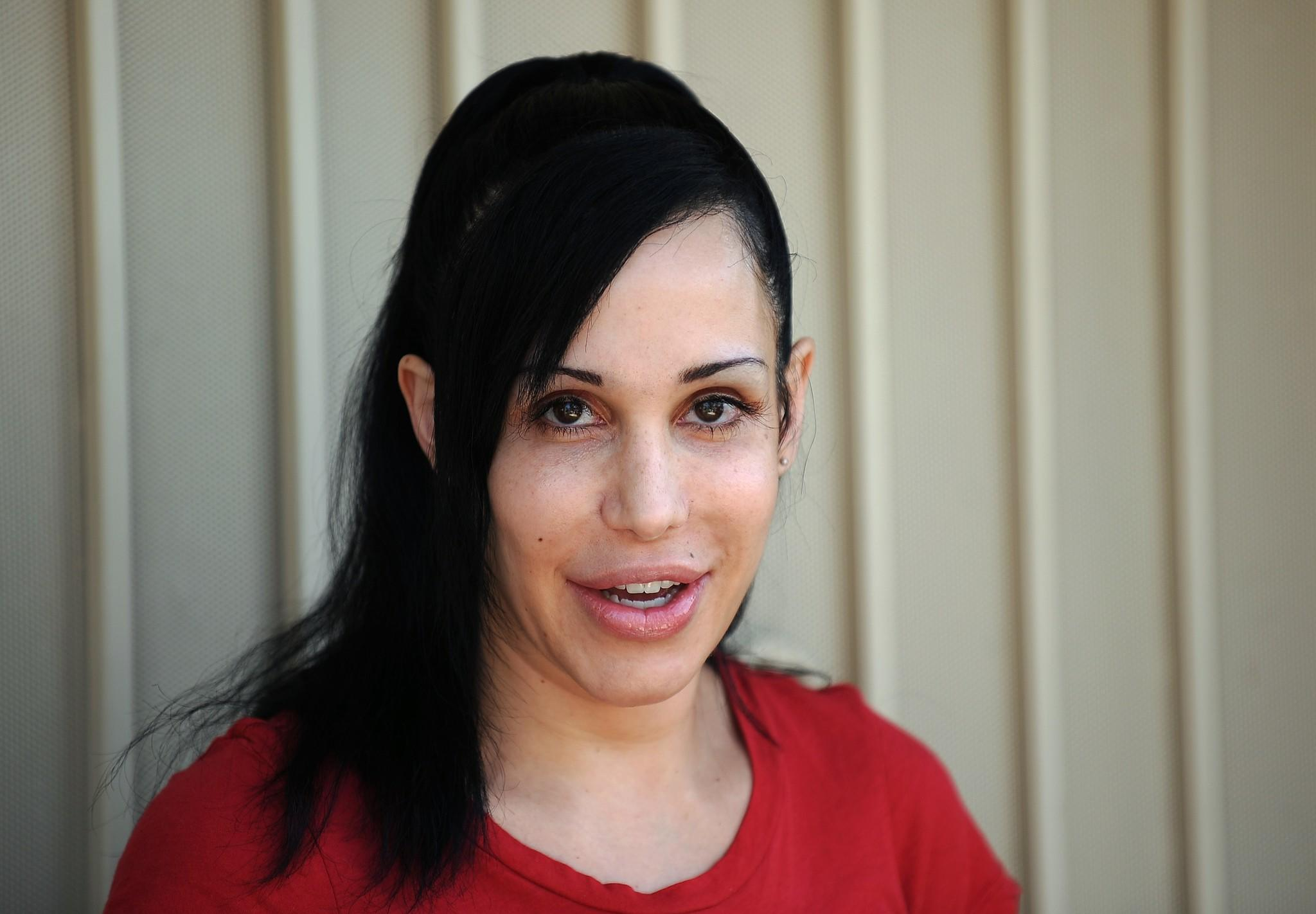 """Octomom"" Nadya Suleman poses for photographers in front of her California home in 2010."