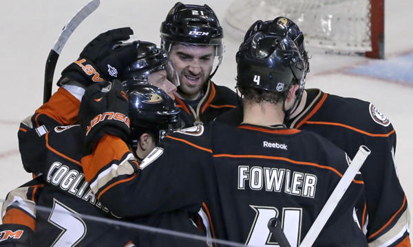 Ducks players celebrate a goal by center Andrew Cogliano, bottom left, during their 1-0 win over the Detroit Red Wings on Sunday.
