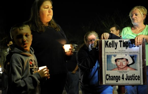 "A supporter falls to the ground crying at a memorial at ""Kelly's Corner"" after two former Fullerton police officers were found not guilty of murder in the 2011 death of transient Kelly Thomas in Fullerton."