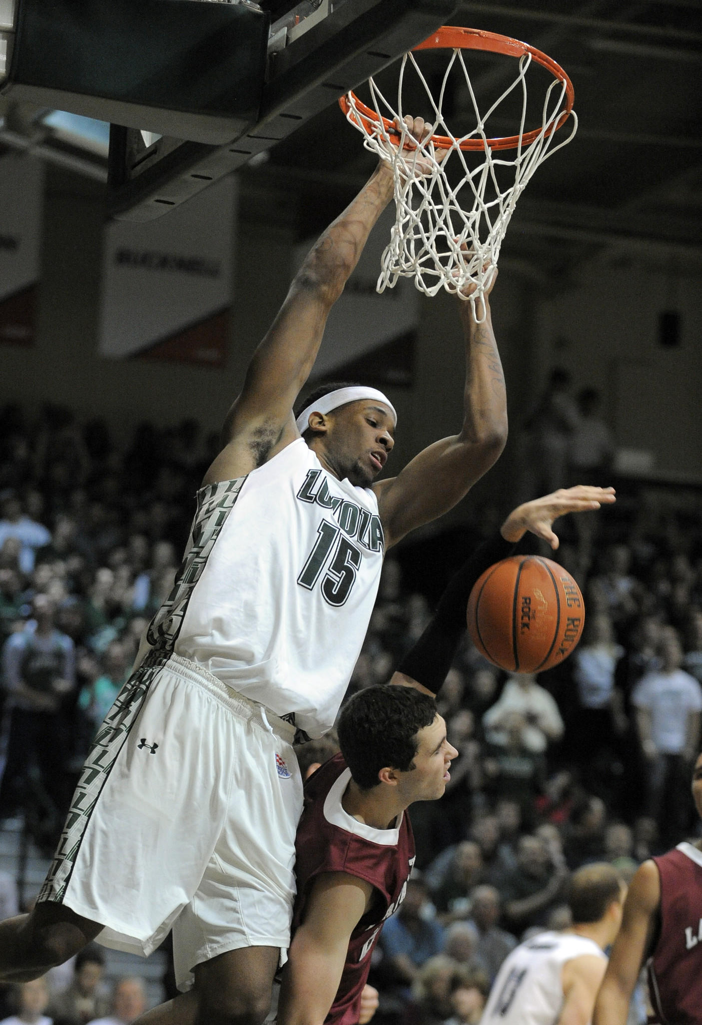 Loyola Maryland's Jordan Latham dunks over Lafayette's Michael Hoffman in the first half.