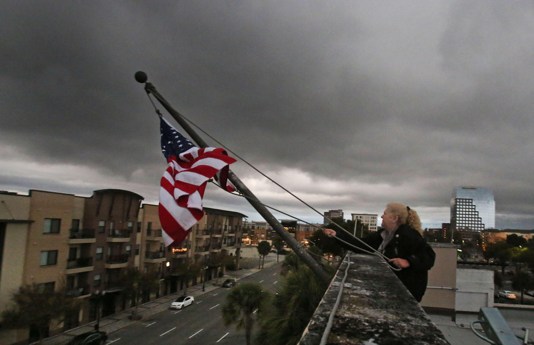 B.J. McMillian, a security officer, atop of the Orlando Sentinel building hoist old glory as a series of cold fronts approach downtown Orlando.