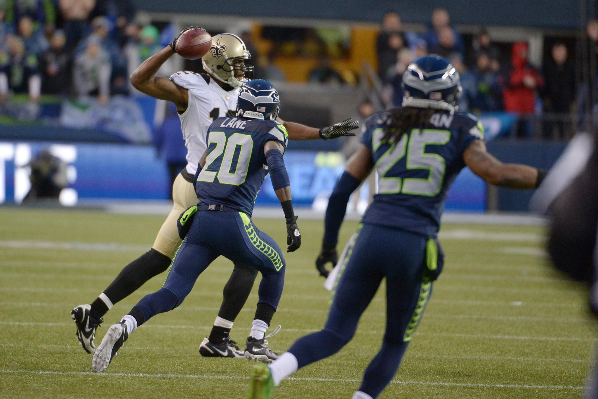 Saints wide receiver Marques Colston (12) throws an illegal forward pass against Seattle Seahawks cornerbacks Jeremy Lane (20) and Richard Sherman (25).
