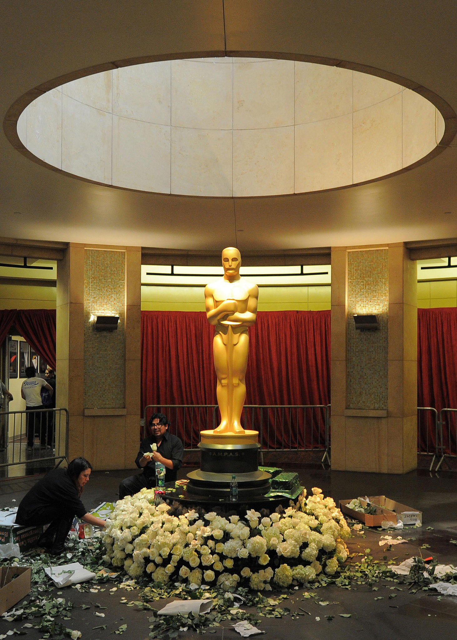 Florists decorate a statue of Oscar in front of the entrance to the Dolby Theatre in preparation one day before the 85th Academy Awards.
