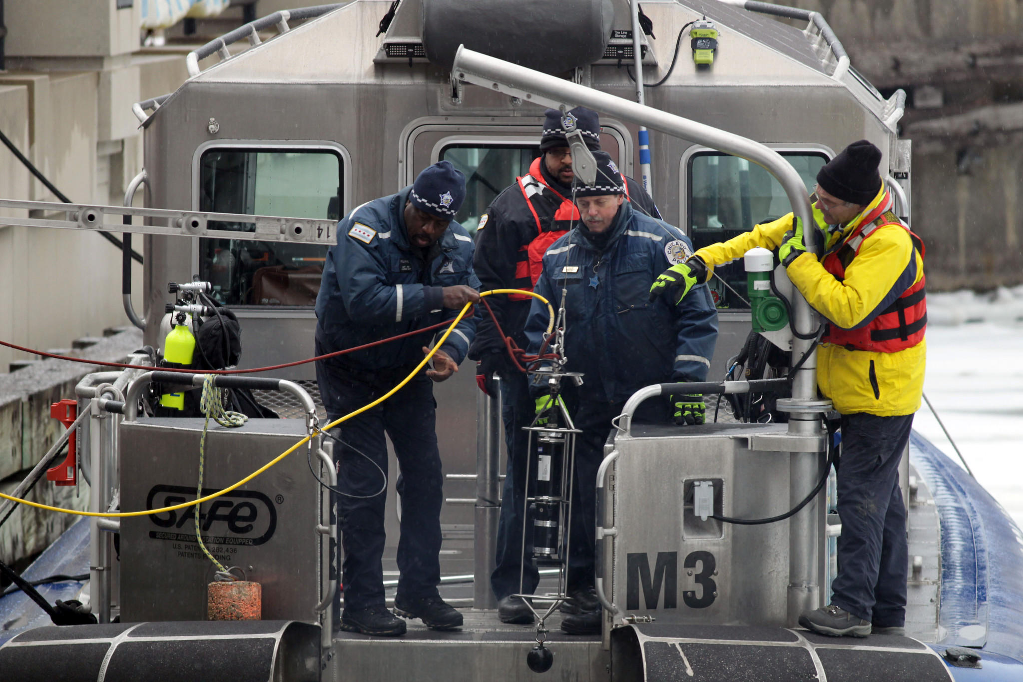 A sonar device is lowered into the river by the Chicago Police Marine Unit.