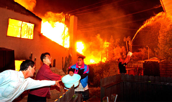 Neighbors use a bucket brigade to fight a fire in the 11700 block of Balboa Boulevard in Granada Hills.