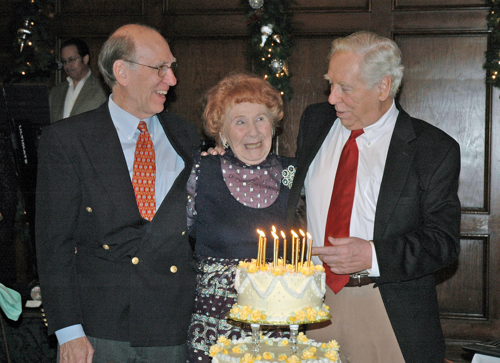 Grace Mylroie Patz, celebrating her 100th birthday, prepares to blow out the candles on her cake with help from her sons Gerry Mylroie, left, and Jim Mylroie at Lakeside Golf Club.