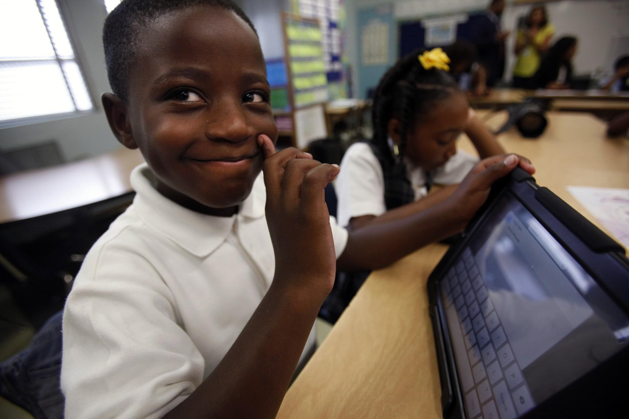 A student smiles as he uses an LAUSD-issued iPad.