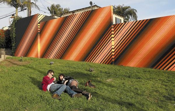 A couple take a break from the Christmas Walk on the triangular parcel of grass adjacent to Hobie Surf Shop in Corona del Mar.