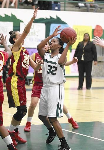 Costa Mesa High's Aubriona Mathis (32), who finished with 18 points, scores in front of Estancia's Lehua Alama-Jordan during an Orange Coast League game on Tuesday at Costa Mesa.