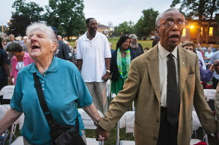 "Sue Hodge and Dr. Sedrick Rawlins, both of Manchester, hold hands while singing ""We Shall Overcome"" at the conclusions of a ceremony in Center Memorial Park commemorating the 50th Anniversary of the March on Washington. Hodge marched in Selma in 1965 and Rawlins was in Washington for the march in 1963."