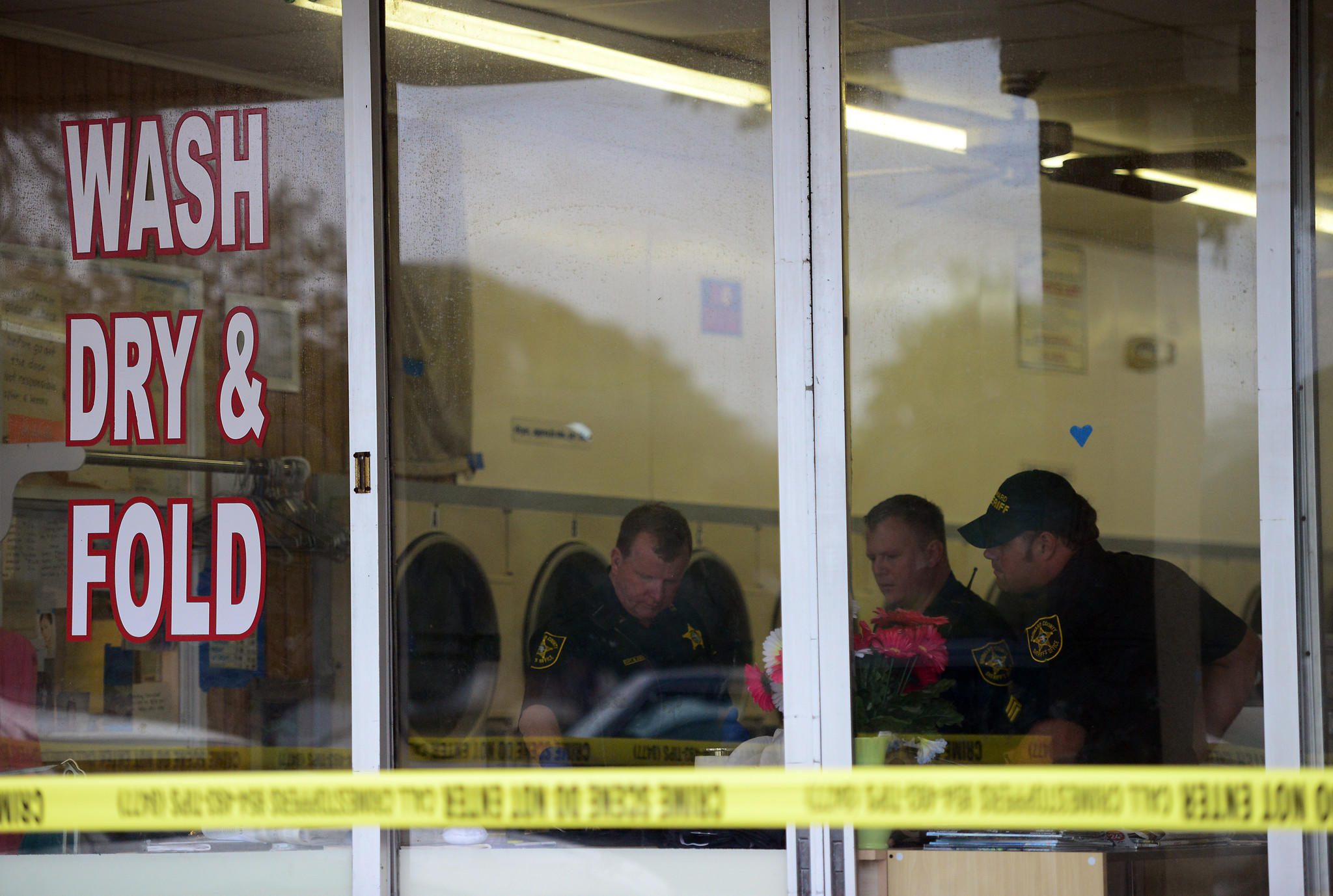 Broward Sheriff's Office works the scene of a laundromat robbery in Pompano Beach on Jan. 15. A patron, who called police, found the owner of the business lying in a pool of blood.