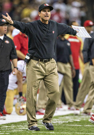 San Francisco Coach Jim Harbaugh sticks to a tried-and-true outfit -- a black sweatshirt tucked into pleated khakis.