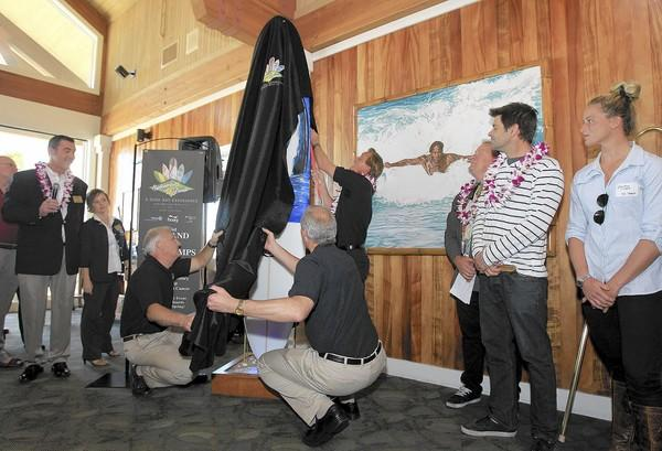 A surfboard by shaper Tim Stamps, second from right, and painter Wyland, who did not attend, is unveiled at Duke's to kick off the opening for Surfboards on Parade, a yearlong exhibit throughout Huntington Beach.