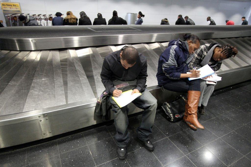 People fill out applications at a job fair for concession employment opportunities at O'Hare International Airport in Chicago.
