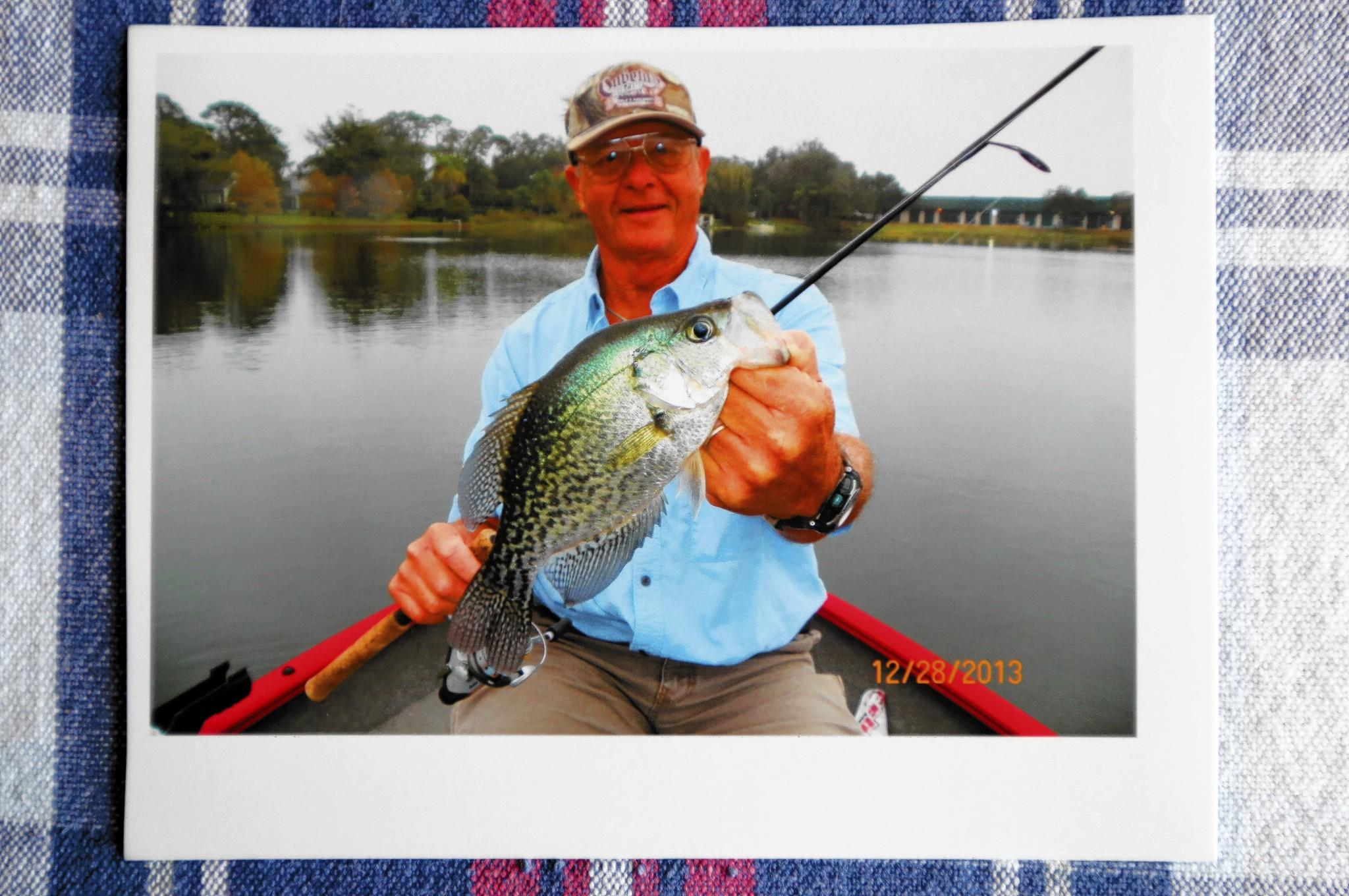 Photo of Pat McDaniel holding a black crappie, his 200,000 catch. McDaniel is a prolific Orlando fisherman who set a record by catching his 200,000th fish.