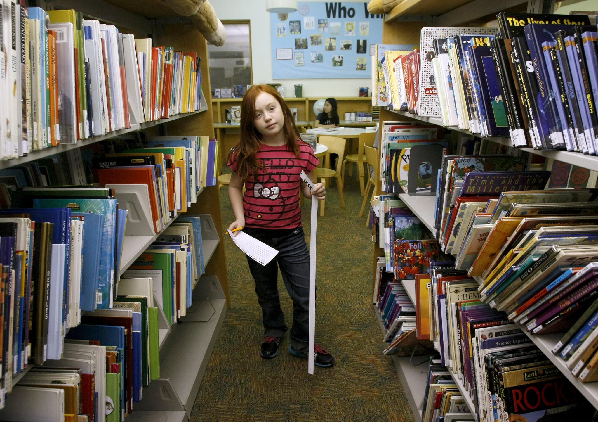 Katrina Polikolsky, 8, of La Crescenta, looks for clues during the How Tall Is It? scavenger hunt at the Montrose Library in Montrose on Wednesday, January 15, 2014. Participating children had to find 13 locations within the library and measure items mentioned in the clues. Once they finished the hunt, they received a small prize.