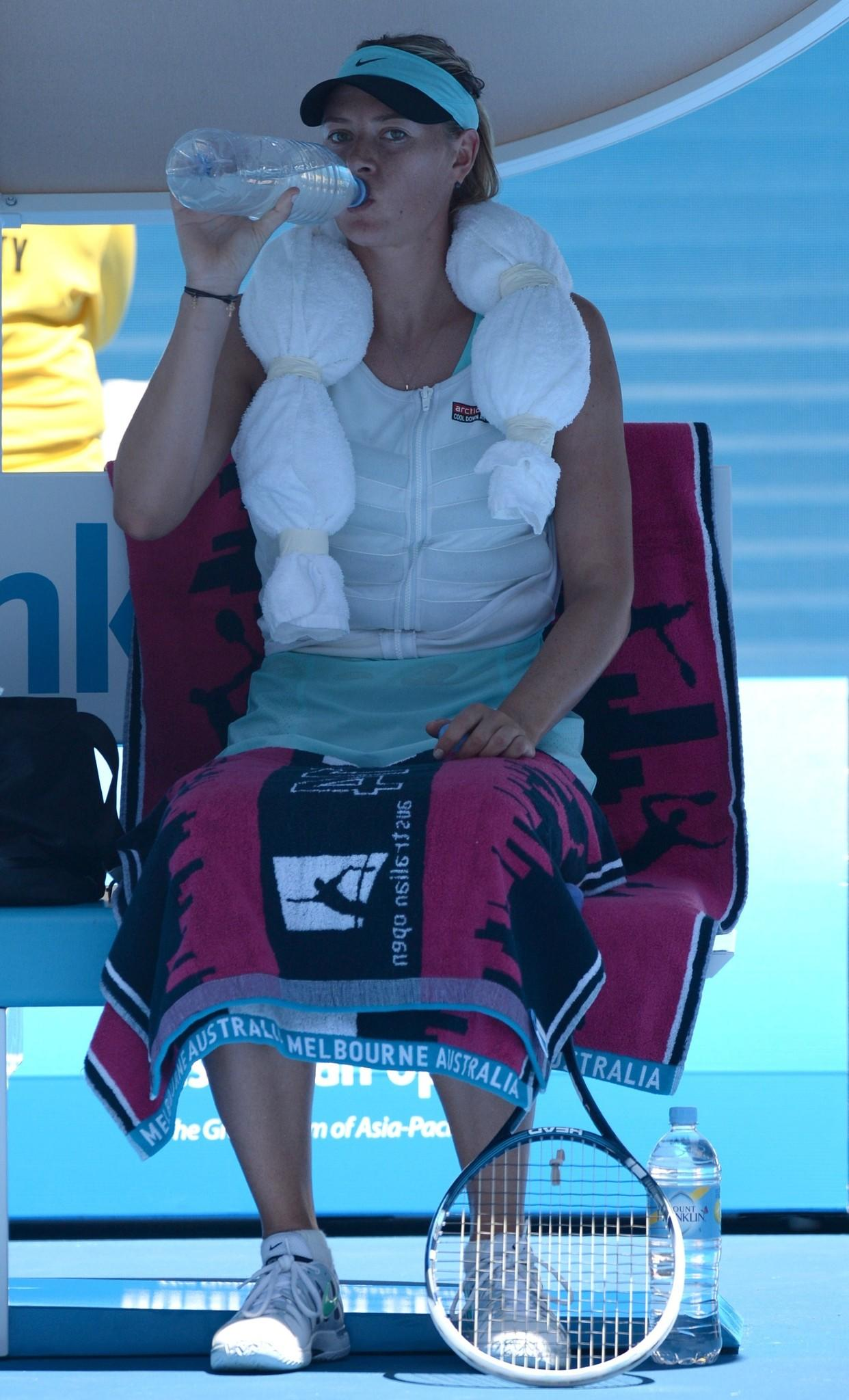 Maria Sharapova drinks as she wears an ice towel during her women's singles match against Italy's Karin Knapp.