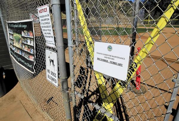 A sign states that Riddle Field is closed for maintenance and repairs from December to February.