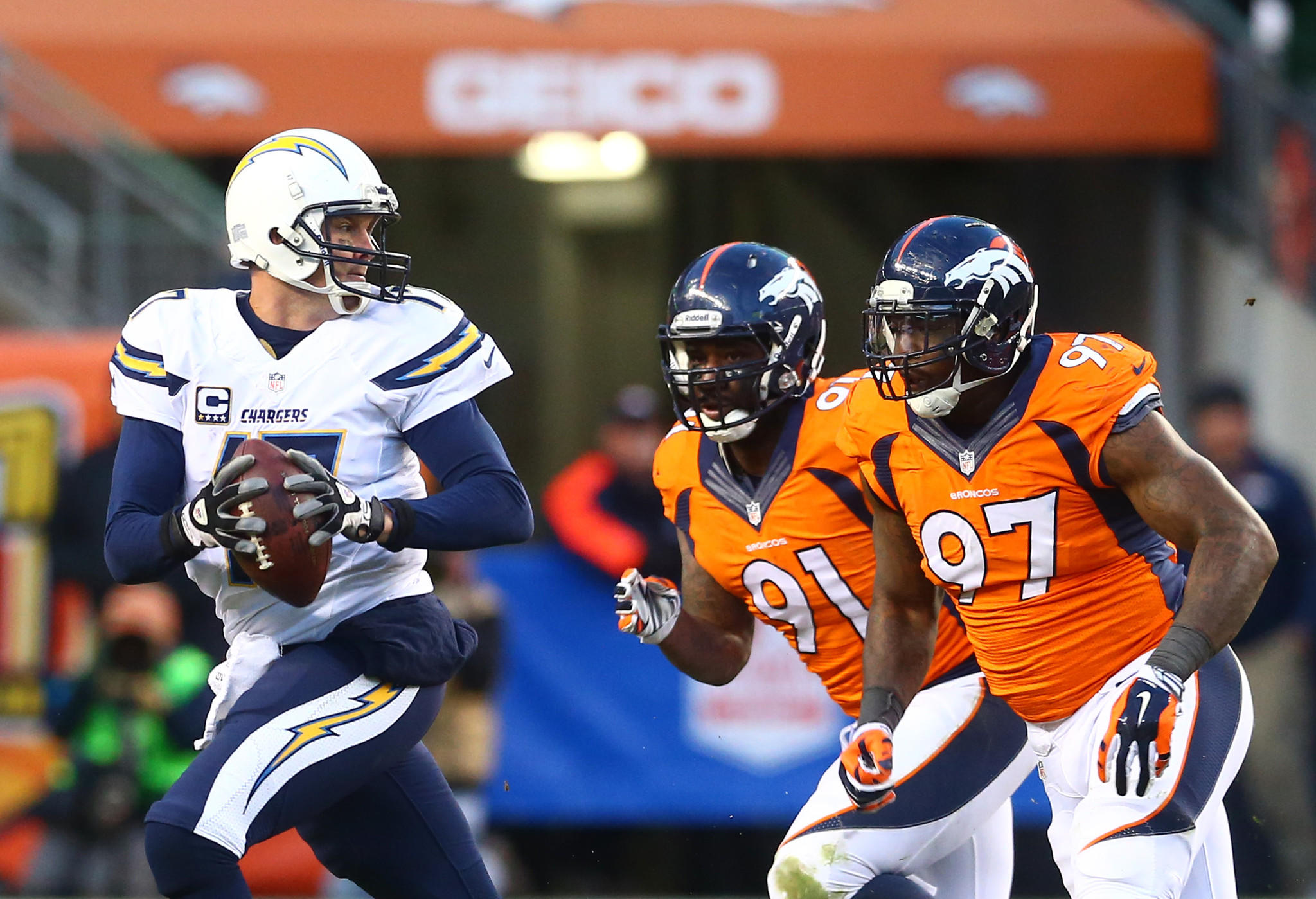 Jan 12, 2014; Denver, CO, USA; San Diego Chargers quarterback Philip Rivers (left) scrambles from Denver Broncos defensive end Malik Jackson (97) and Robert Ayers (91) in the second half during the 2013 AFC divisional playoff football game at Sports Authority Field at Mile High. Denver defeated San Diego 24-17.