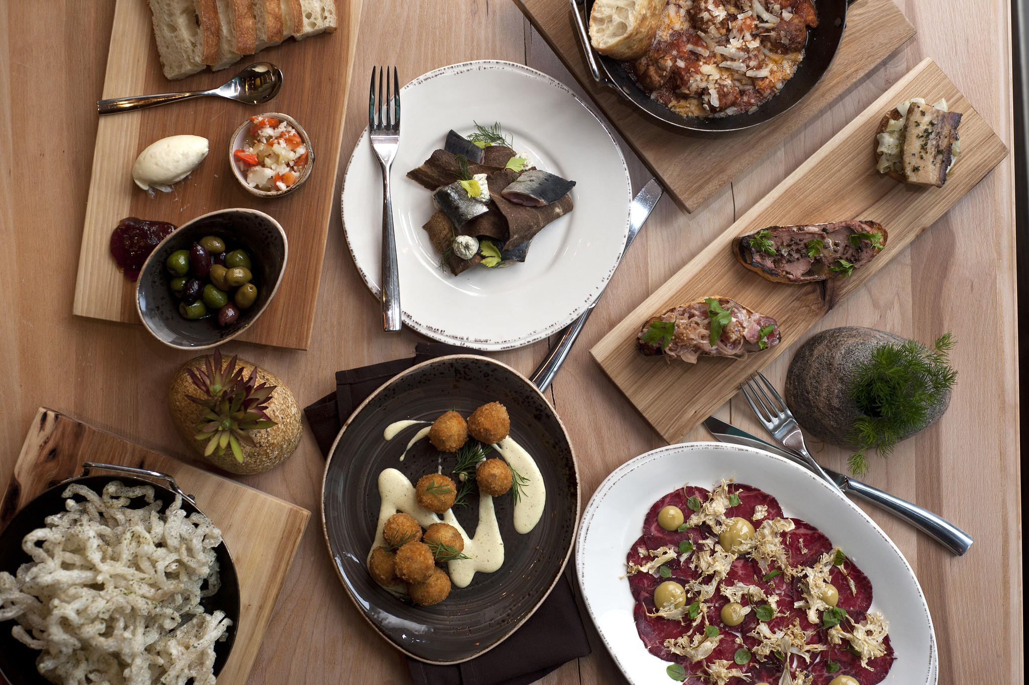 Dishes at Cicchetti (clockwise from top left): olives with foccacia, sardines, meatballs, bruschette, steak carpaccio, cod and prosciutto croquettes and pork cracklins