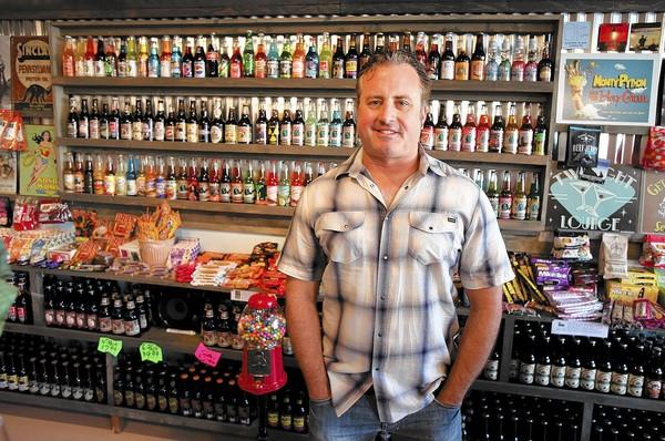Mark McLaughlin stands in front of a wall of Rocket Fizz brand soda at the new Rocket Fizz Soda Pop and Candy Shop in Laguna Beach.