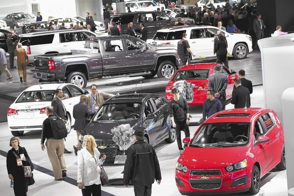 Visitors on Tuesday look over cars at the North American International Auto Show in Detroit.