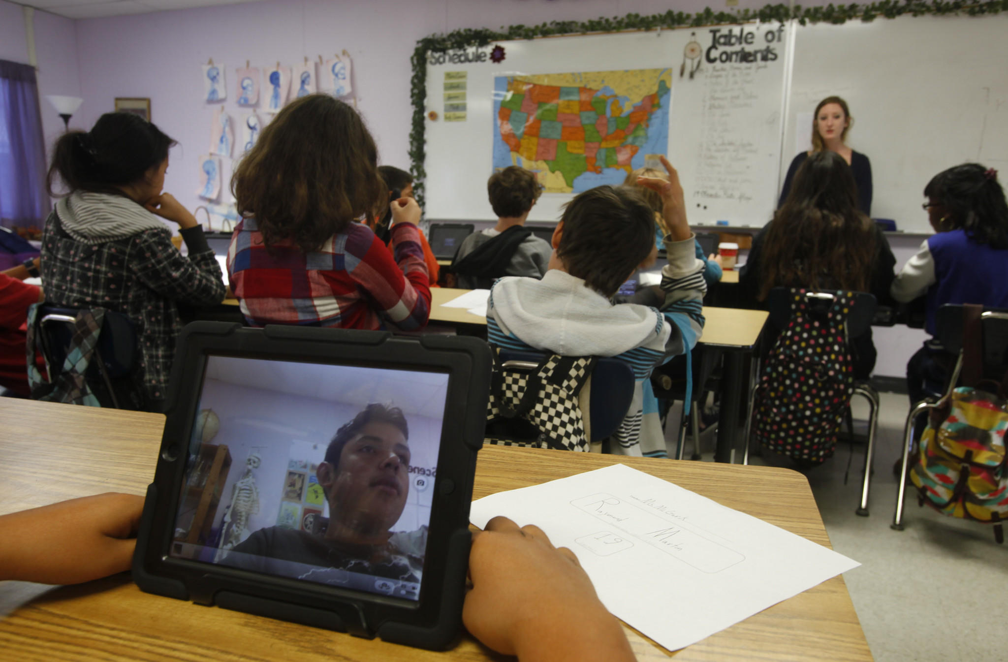 Stephanie McGurk's eighth-grade class at Ocean Charter School turn on their L.A. Unified-distributed iPads this week for the first time.