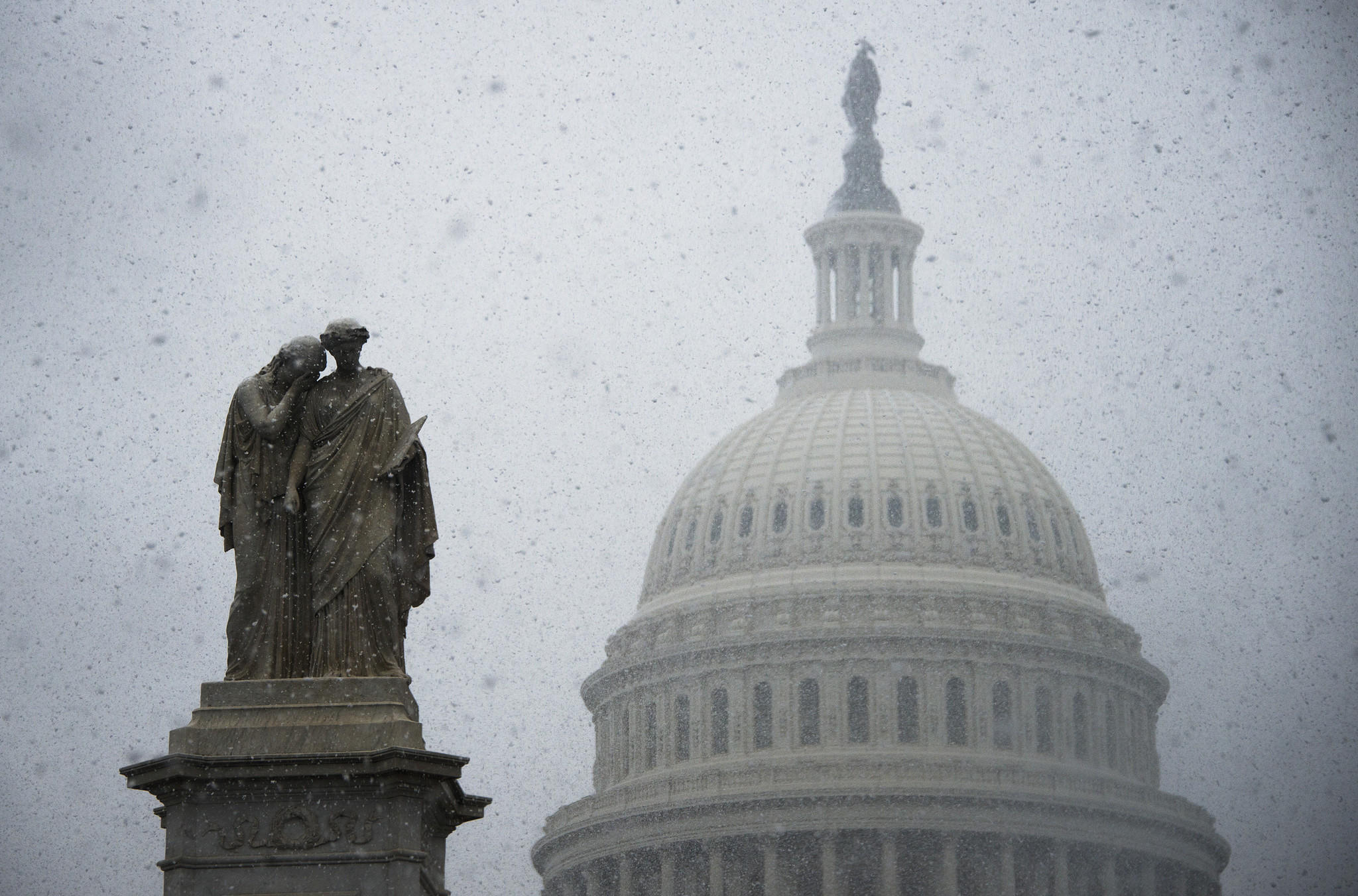 Snow gathers on a statue outside the US Capitol Building in Washington.