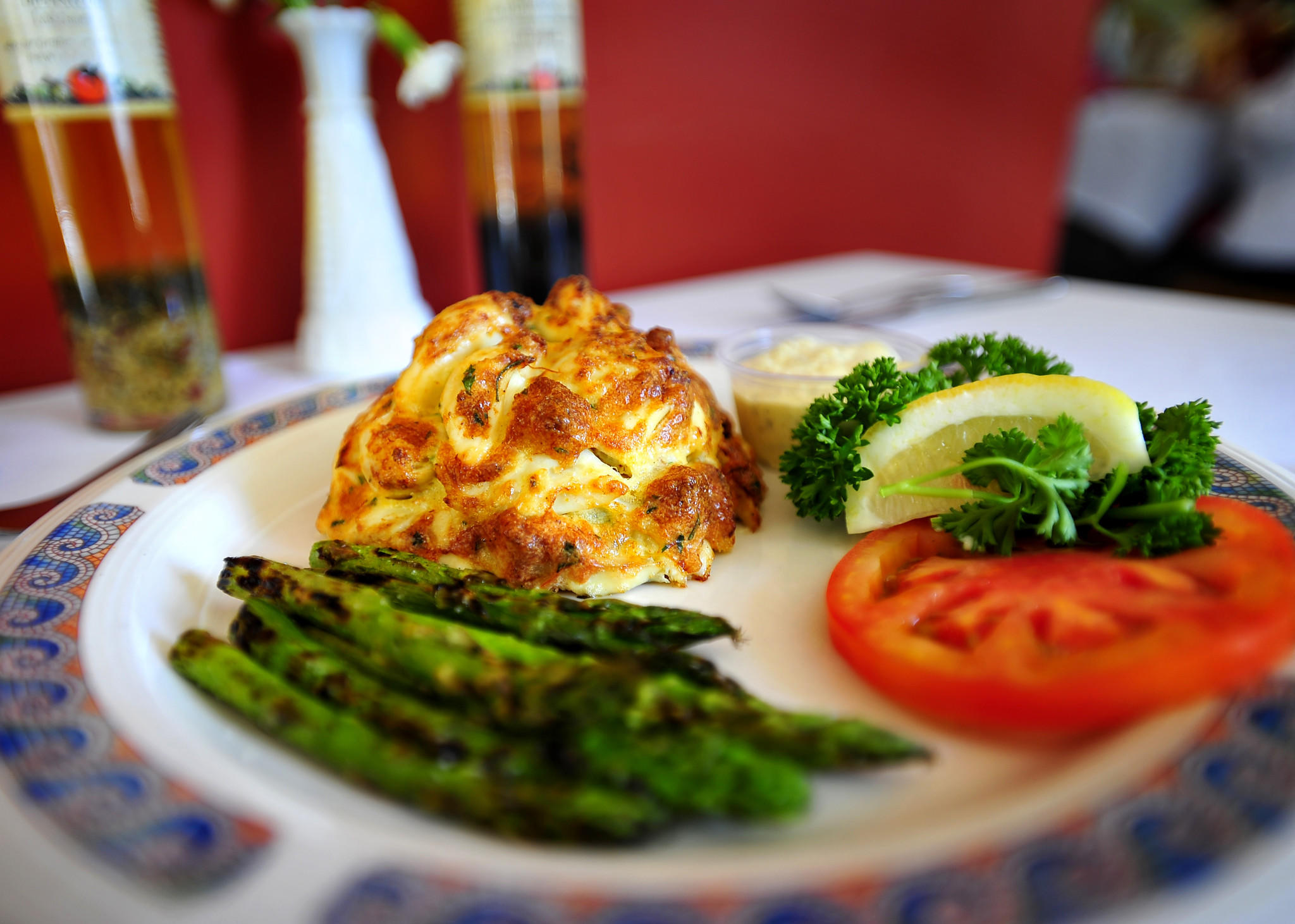 Pappas' Famous Crabcake served with grilled asparagus and lemon, tomato, and parsley to garnish.
