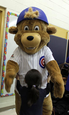 "New Cubs mascot ""Clark"" is about to give a big hug to a student as the Cubs Caravan comes to Pablo Casals Elementary School on Chicago's northwest side."