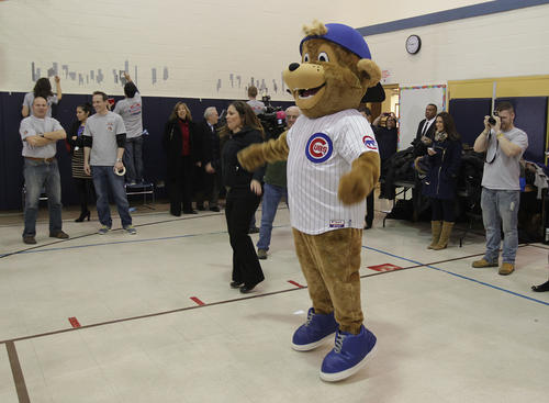 """New mascot """"Clark"""" does some jumping- jacks with the kids."""