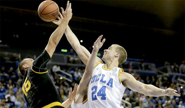 Travis Wear blocks a shot by Arizona State's Egor Koulechov during UCLA's 87-72 victory Sunday over the Sun Devils.